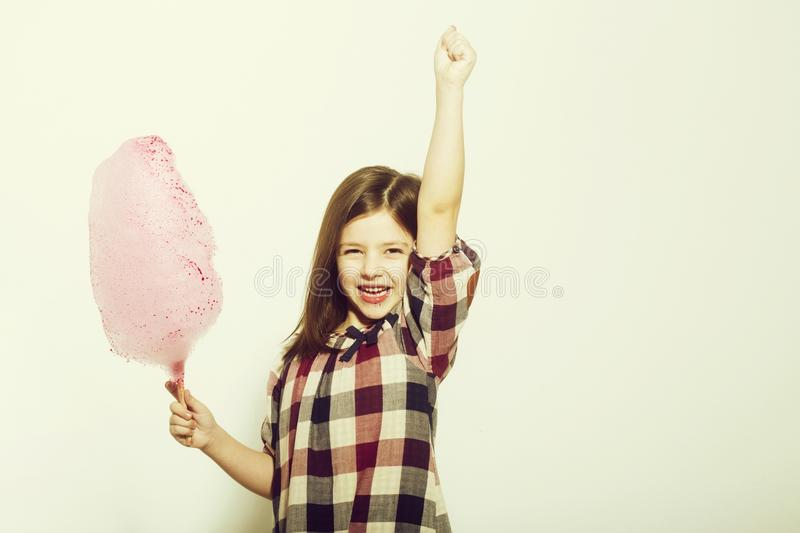Happy cute girl smiling with cotton candy on stick. Candyfloss. Happy, cute girl, small, little, child in plaid dress smiling with tasty, pink, cotton candy stock images