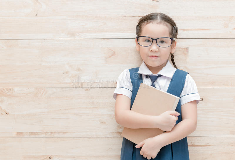 Happy cute girl student in uniform with book royalty free stock images