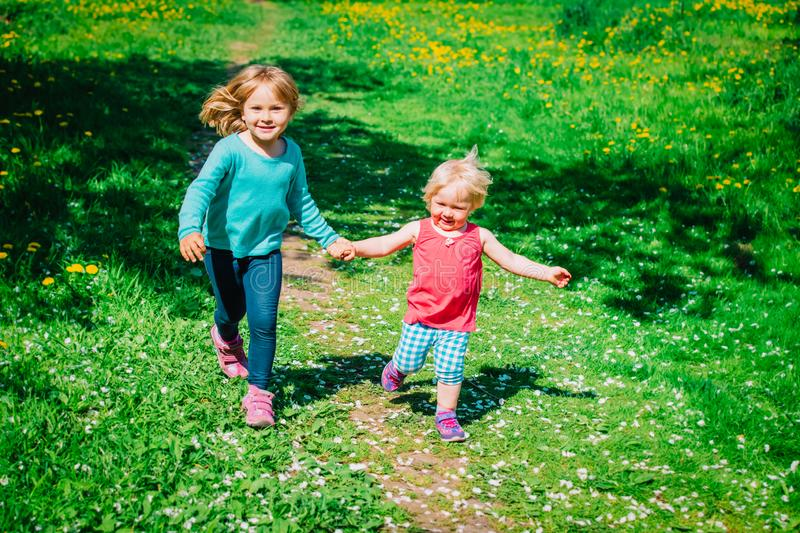 Happy cute girls play run in spring nature stock image