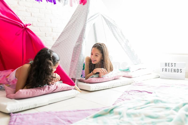 Girls Sharing Gossips While Resting In Tents During Pajama Party stock photos