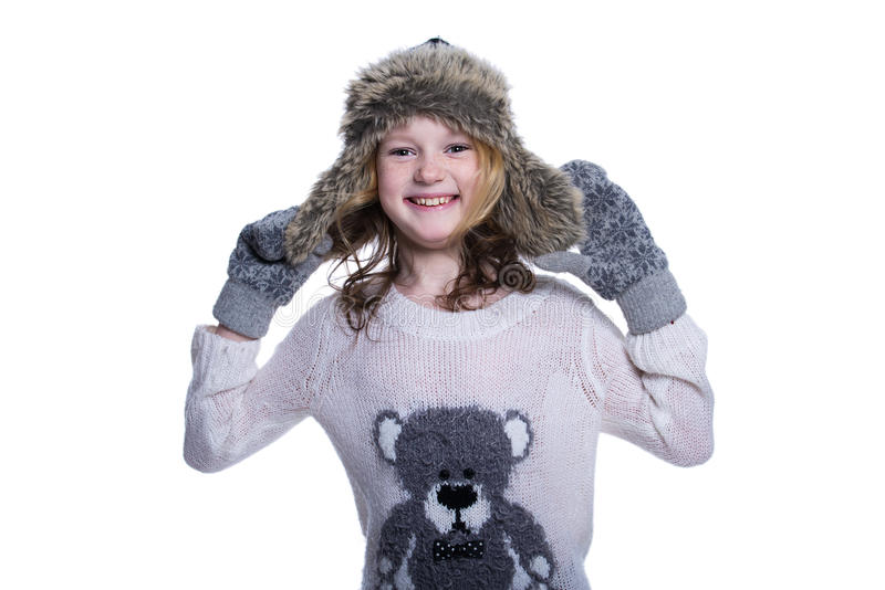 Happy cute kid posing in the studio isolated on white background. Wearing winter clothes. Knitted woolen sweater, scarf, hat royalty free stock photography