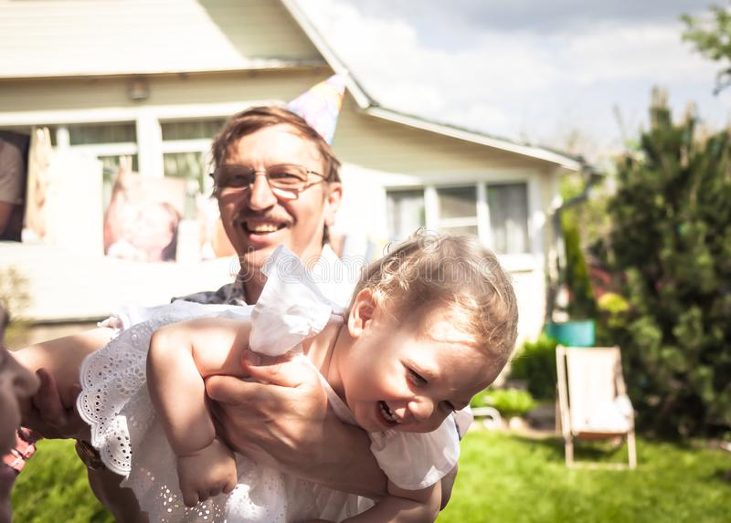 Happy cute laughing baby girl having fun with active senior grandfather outdoors on backyard stock photos