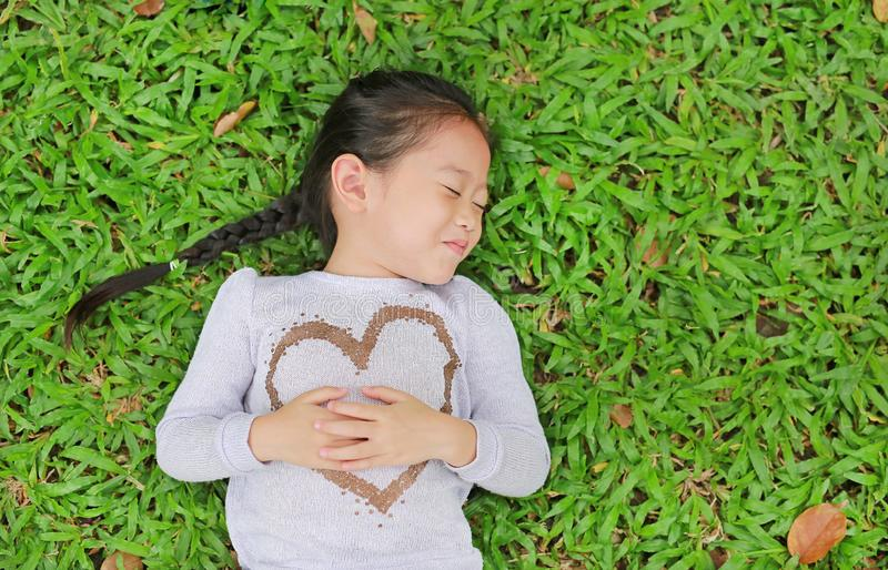 Happy cute little Asian child girl lying on green lawn. Smiling and closed her eyes stock photo