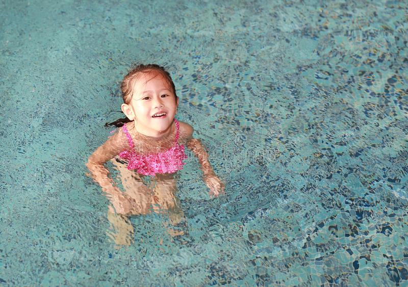 Happy cute little Asian child girl playing in pool.  stock photography