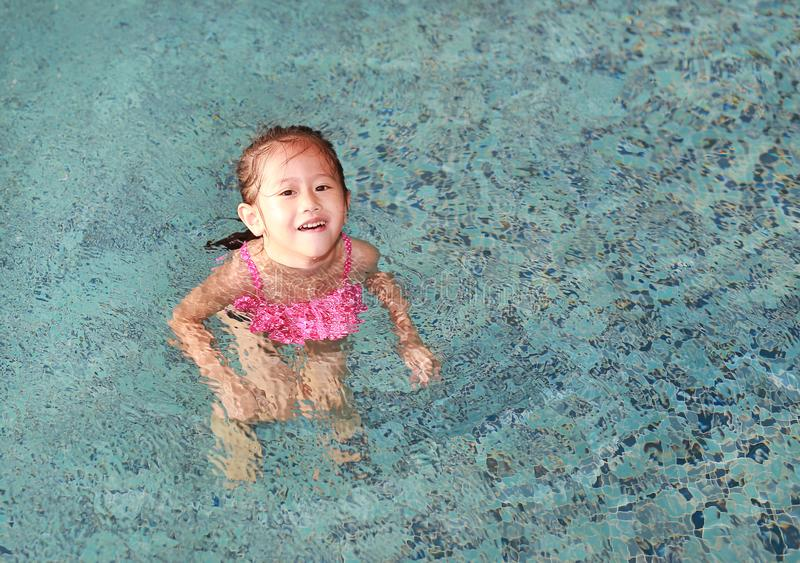 Happy cute little Asian child girl playing in pool.  stock images