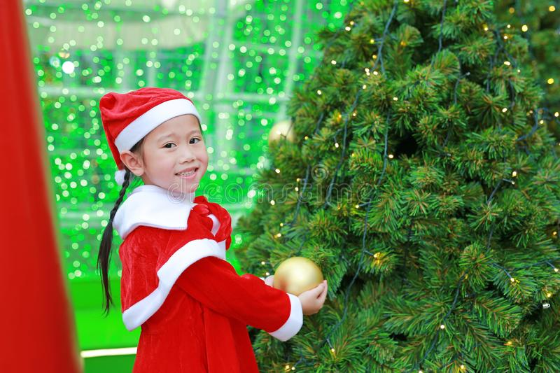 Happy cute little Asian child girl in Santa costume near Christmas tree and background. Christmas winter holiday concept.  royalty free stock images