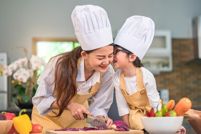 Happy cute little boy with eyeglasses kissing beautiful Asian woman mother while prepare to cooking in kitchen at home. People royalty free stock photos