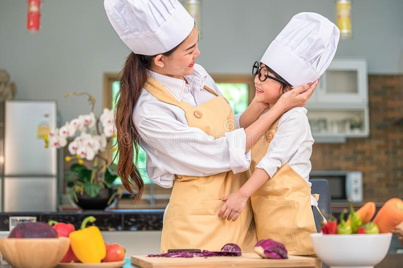 Happy cute little boy with eyeglasses looking beautiful Asian woman mother each other while prepare to cooking in kitchen at home stock image