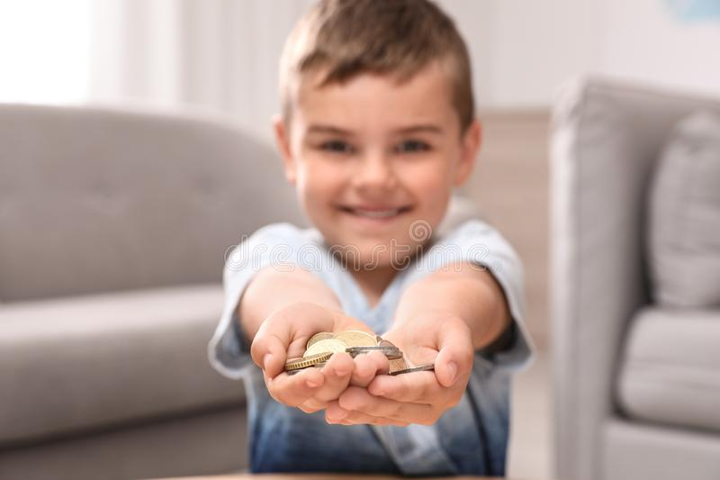 Happy cute little boy holding coins at home royalty free stock image