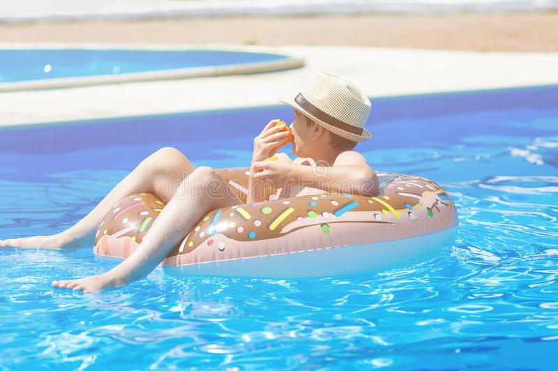 Happy cute little boy teenager lying on inflatable donut ring with orange in swimming pool. Active games on water, vacation. Holidays concept. Chocolate donut stock images
