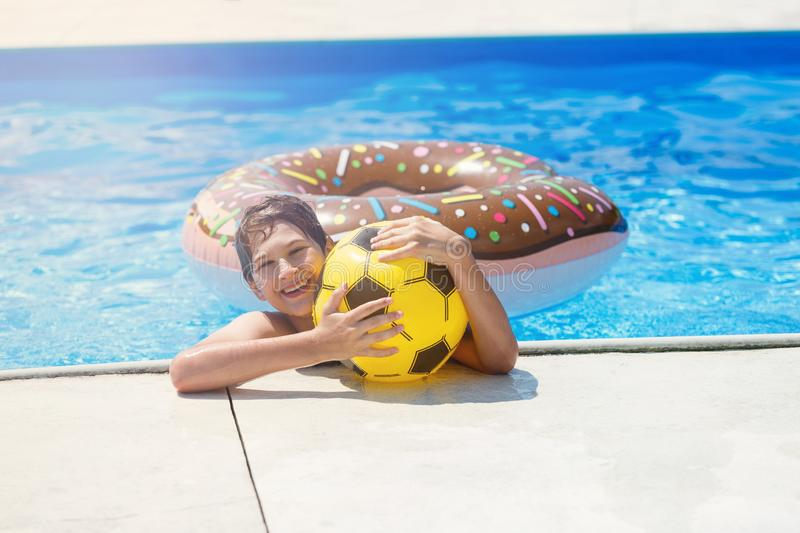 Happy cute little boy teenager in swimming pool. Active games on water, vacation, holidays concept. Chocolate donut. Cool fun summer holidays for children royalty free stock photos