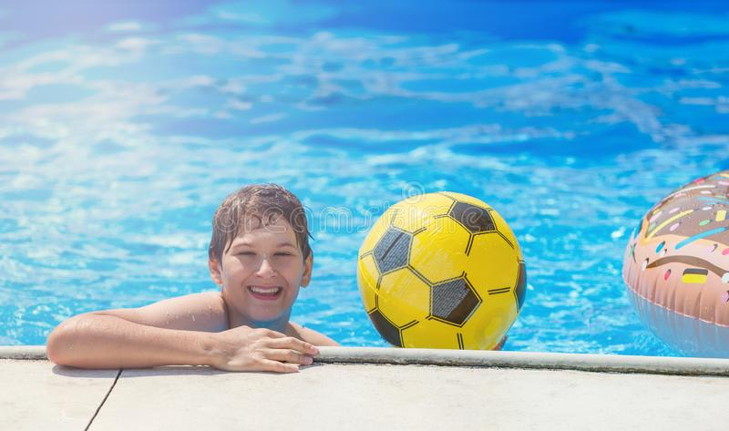 Happy cute little boy teenager in swimming pool. Active games on water, vacation, holidays concept. Chocolate donut. Cool fun summer holidays for children stock photos