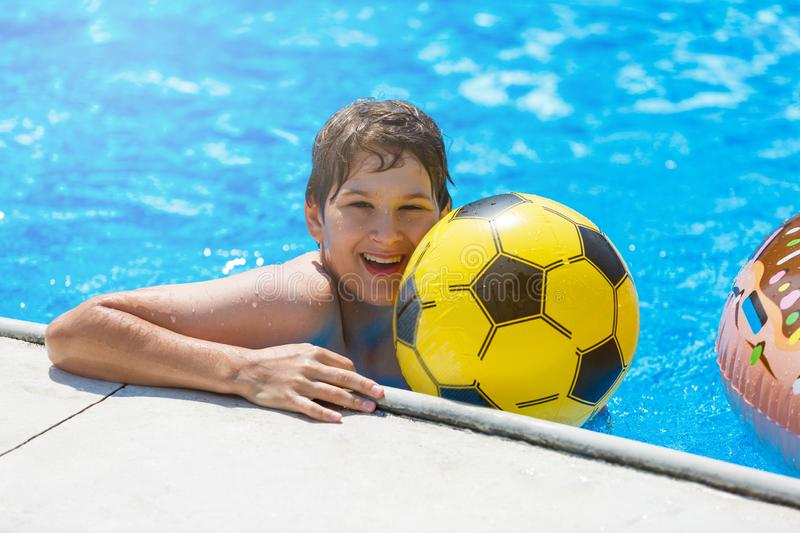 Happy cute little boy teenager in swimming pool. Active games on water, vacation, holidays concept. Chocolate donut. Cool fun summer holidays for children royalty free stock photo