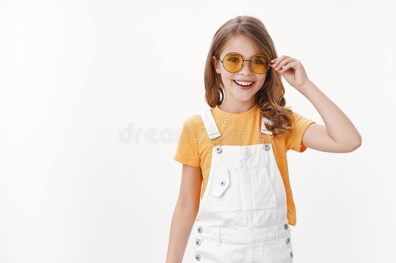 Happy cute little fashionable girl, daughter wearing yellow round sunglasses, t-shirt and dungarees, put on glasses and royalty free stock images