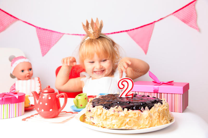 Happy cute little girl at birthday party. Happy cute little girl with sweets and dolls at birthday party stock image