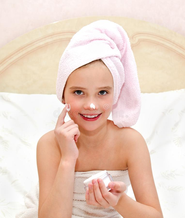 Happy cute little girl child applying cream. At home royalty free stock images