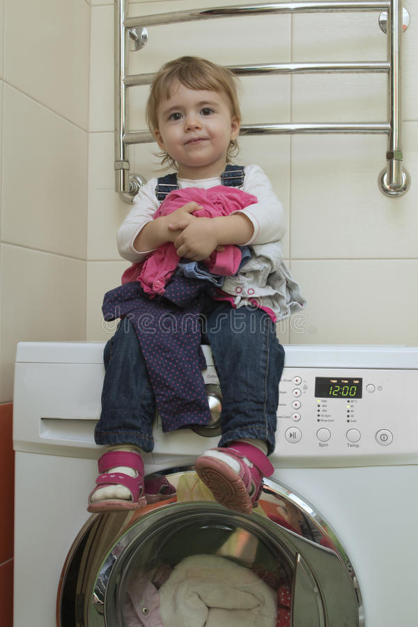 Happy Cute Little Girl With Clothes Sitting On The Washing Machine