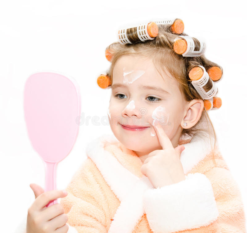 Happy cute little girl in hair curlers with mirror applying cream stock photography