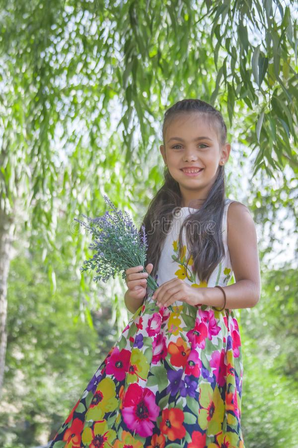 Cute little girl holding bouquet of lavender in park royalty free stock photo