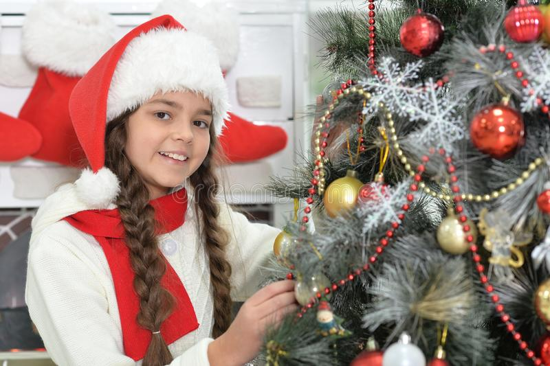 Cute little girl in Santa hat decorating Christmas tree stock photos