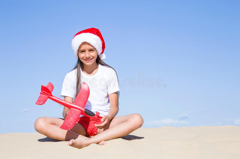 Happy cute little girl wearing a red Santa hat sitting on the sandy beach by the sea and holding a red toy plane on clear sunny da. Christmas celebration stock photography
