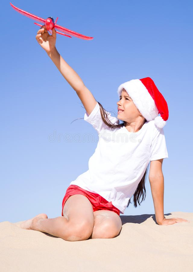 Happy cute little girl wearing a red Santa hat sitting on the sandy beach by the sea and playing with a red toy plane on clear sun. Christmas celebration stock photos