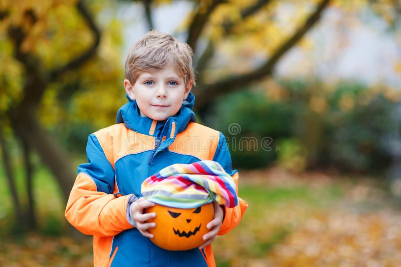 Happy cute little kid boy with halloween pumpkin lantern on autu. Happy cute little kid boy with halloween pumpkin lantern. Funny child in colorful clothes stock photography