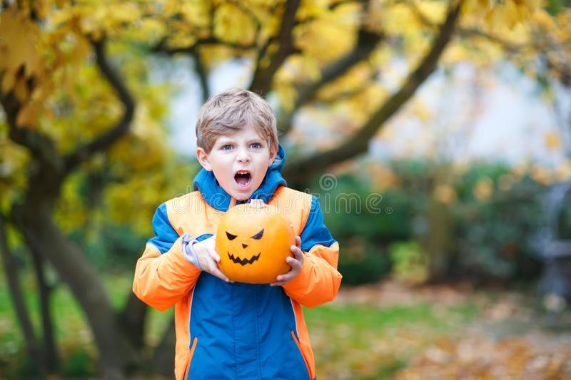 Happy cute little kid boy with halloween pumpkin lantern. Funny child in colorful clothes having fun and playing in. Autumn garden on cold autumnal day. Scary stock photo