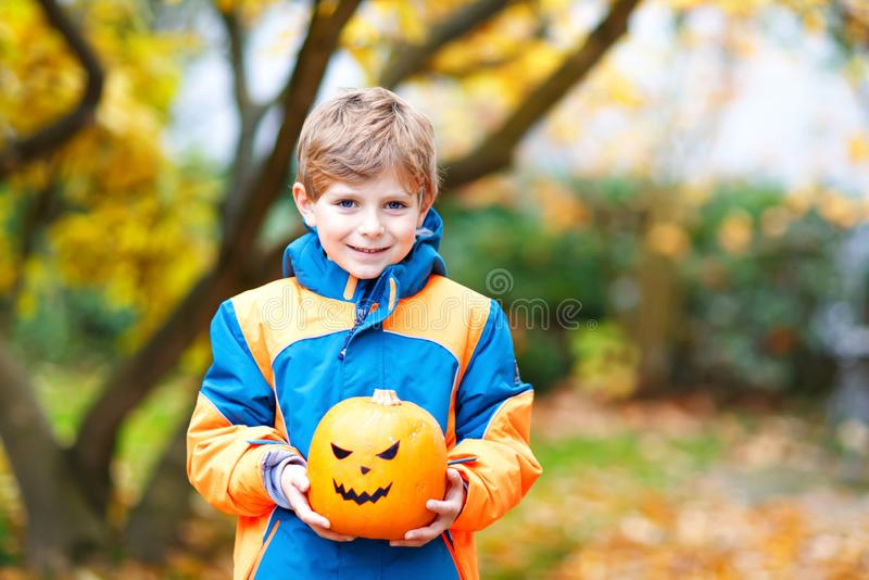 Happy cute little kid boy with halloween pumpkin lantern. Funny child in colorful clothes having fun and playing in. Autumn garden on cold autumnal day. Scary royalty free stock image