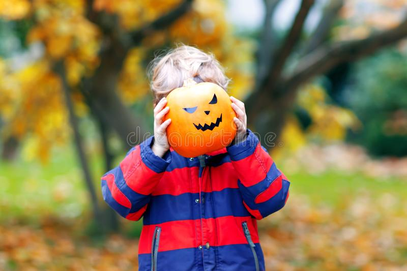 Happy cute little kid boy with halloween pumpkin lantern. Funny child in colorful clothes having fun and playing in. Autumn garden on cold autumnal day. Scary stock image