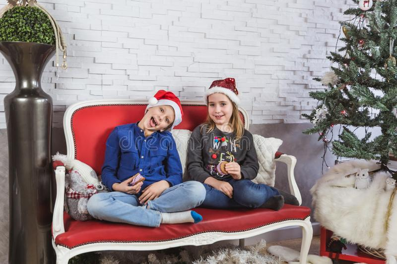Happy cute little kids in Santa hats eating delicious cookies at home royalty free stock photos