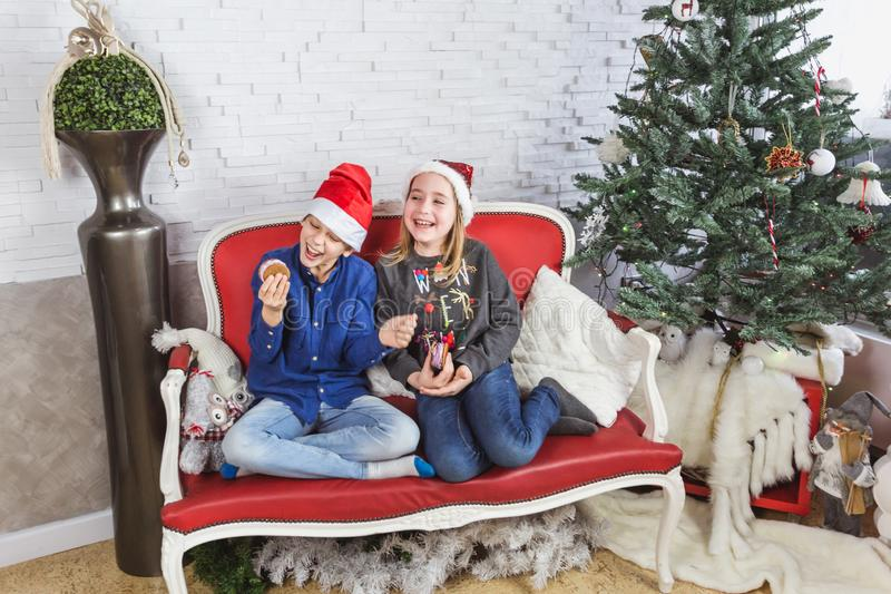 Happy cute little kids in Santa hats eating delicious cookies at home royalty free stock image