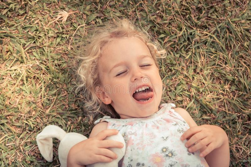 Happy cute mischievous smiling child girl fooling lying on grass concept happiness carefree childhood lifestyle stock image