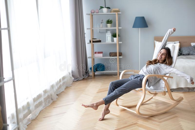 Happy cute pretty woman lying in the armchair on the weekend and stretching stock photos
