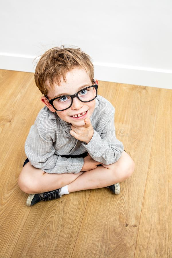 Happy cute schoolboy with serious eyeglasses and tooth missing seated stock photos