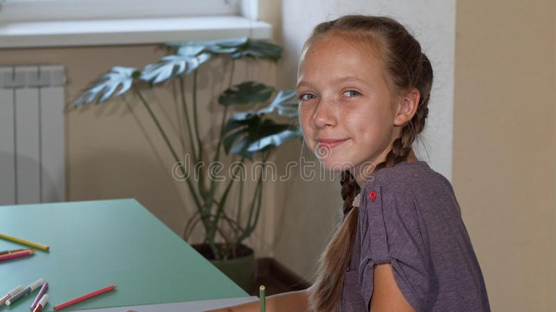 Happy cute schoolgirl smiling to the camera over her shoulder while drawing royalty free stock images