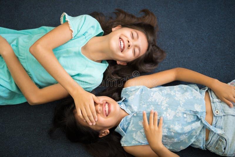 Happy cute siblings enjoying playing peek a boo royalty free stock photos
