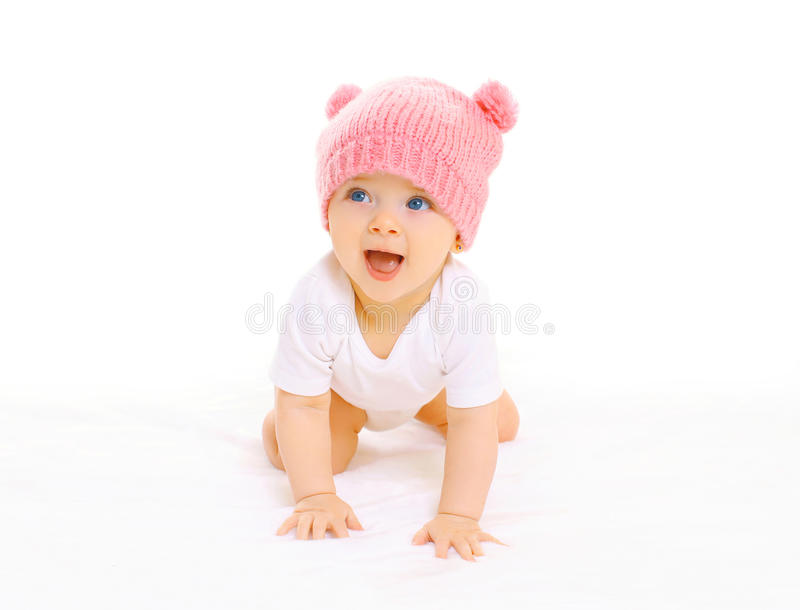 Happy cute smiling baby in knitted pink hat crawls on a white royalty free stock images