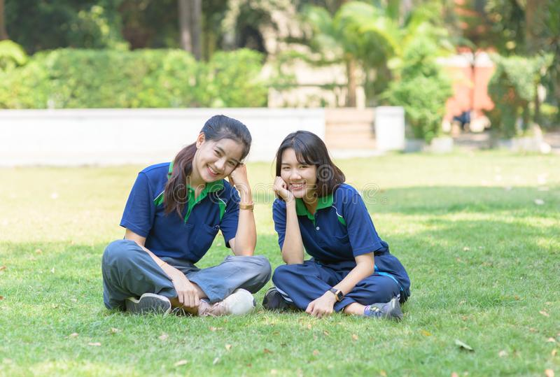Happy cute students smile and sitting on grass stock photography