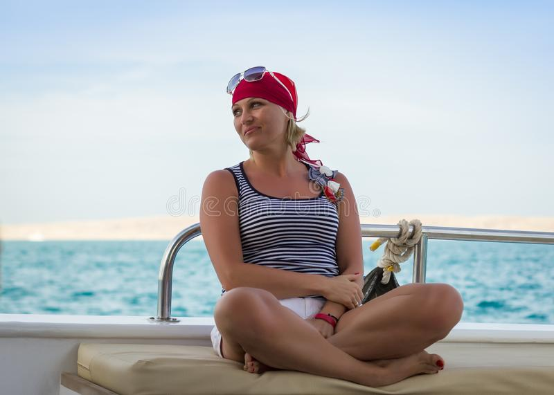 Happy cute sunburnt girl in a red bandana is sitting on a yacht on background of the blue sky and blue sea stock images