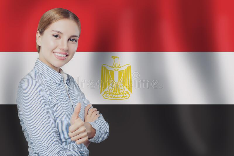 Happy cute woman student with thumb up on the Egypt flag. Background. Egypt, travel and learn arabic language concept stock photo