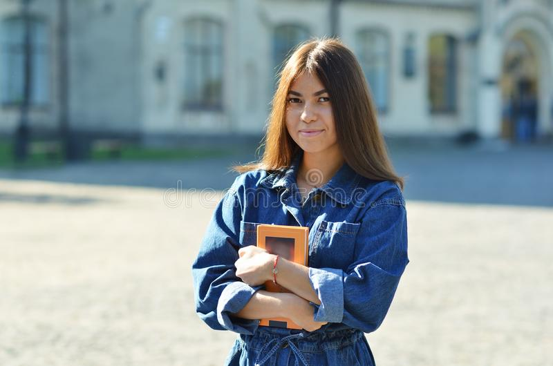 Happy cute young woman student holding books and walking royalty free stock image