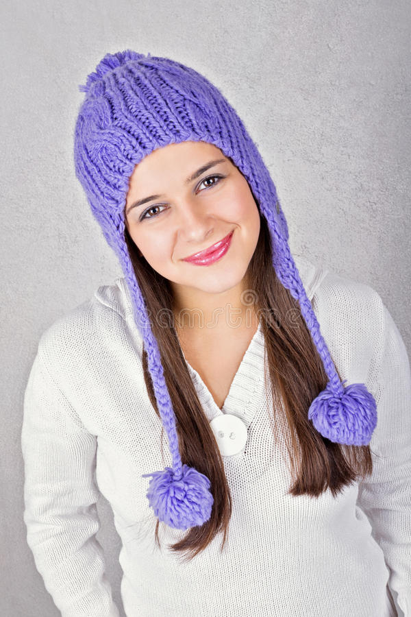 Happy cute young woman wearing purple beanie hat. Happy cute Caucasian brunette young teenage girl wearing purple beanie hat and white sweater smiling looking at stock photography