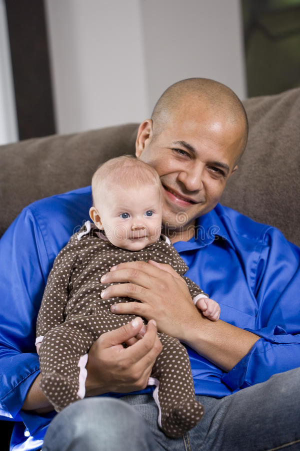 Happy dad with baby sitting on lap. Happy dad with 3 month old baby sitting on lap royalty free stock images