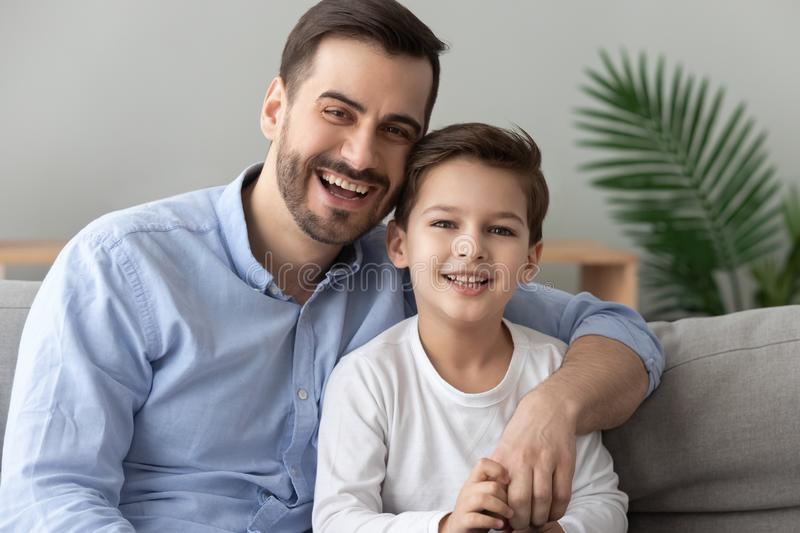 Happy dad embracing son looking at camera sit on sofa. Happy male family cheerful young adult single dad embracing cute child preschool boy looking at camera royalty free stock image