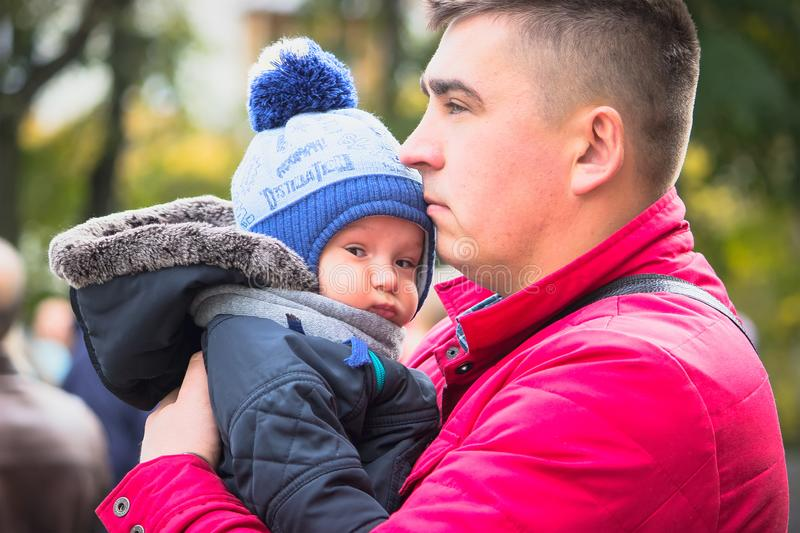 Happy dad holding his son, little funny kid boy on arm, on cold day, standing together in autumn park stock photo