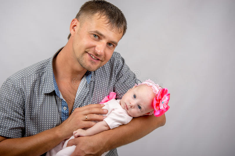 Happy dad is holding a two-month girl. Young dad sitting on a bed and holds her two-month baby daughter stock photography