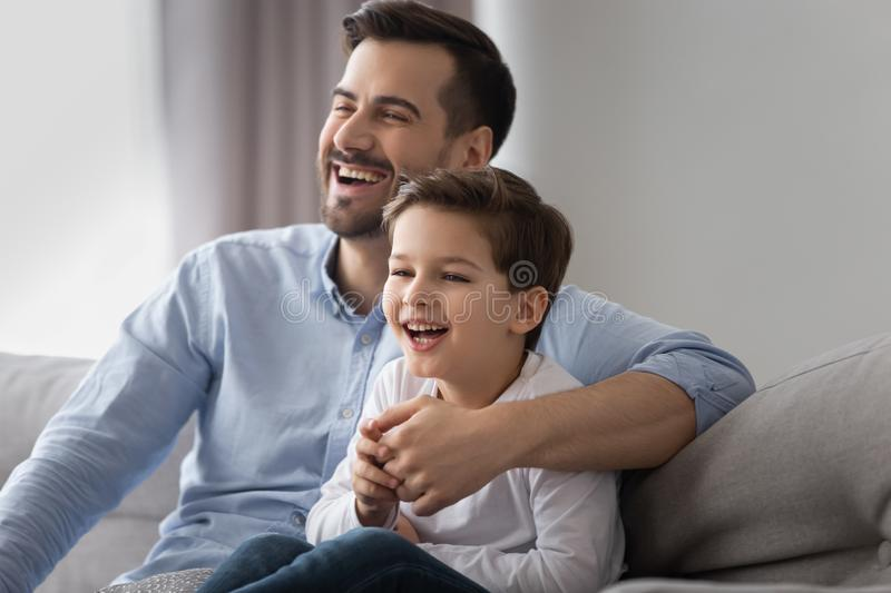 Happy dad and kid son laughing watching tv on sofa. Happy young dad and cute small kid son laughing watching funny comedy movie tv show sitting on sofa, cheerful royalty free stock photo