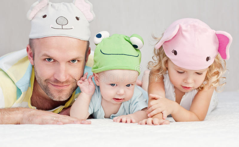 Happy dad with kids in funny hats stock images