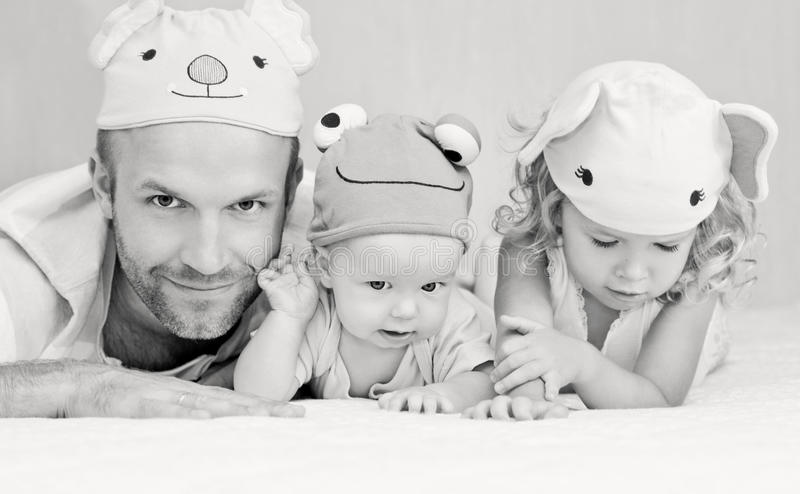 Happy dad with kids in funny hats royalty free stock photography